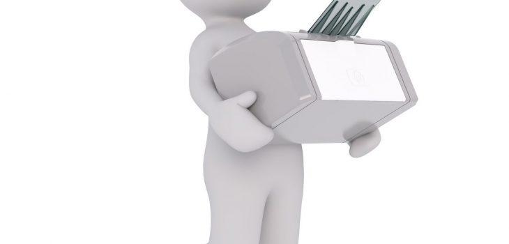 Figurka białego mężczyzny niosącego drukarkę